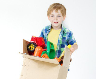 Child with cardboard box of toys