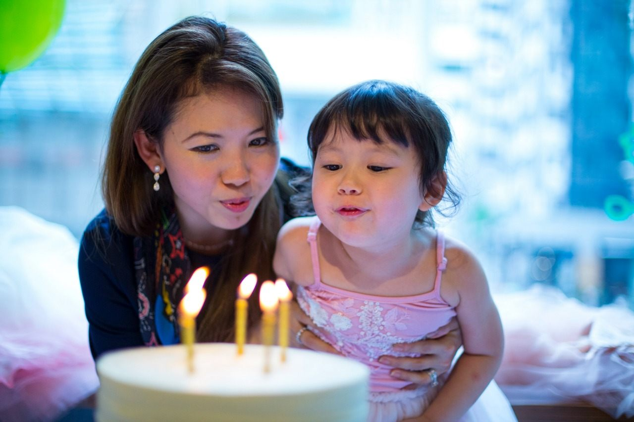 mum and child blowing out birthday cake candles