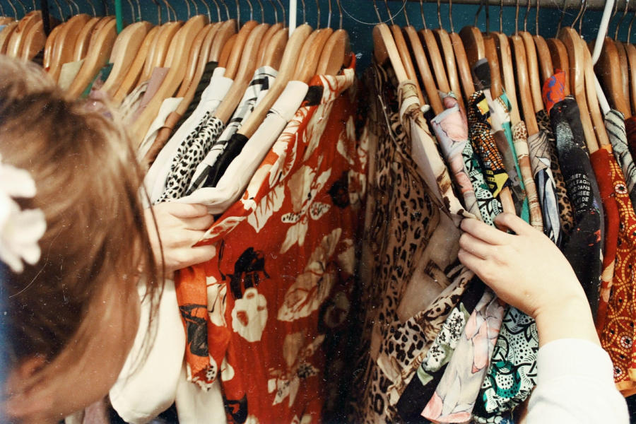 woman thrift shopping for secondhand clothing